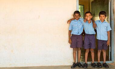 3 Jungs stehen vor einer Schule