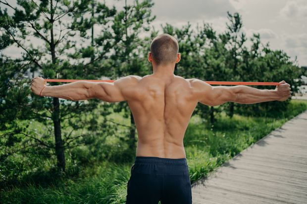 Back,View,Of,Unrecognizable,Sportsman,Stretches,Elastic,Resistance,Band,,Demonstrares