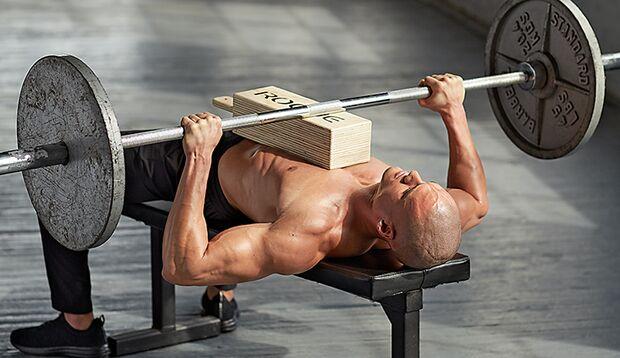 Beim Bankdrücken unterstützt ein Yogaklotz auf Brust und Bauch
