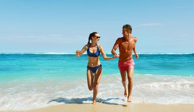 Ein Paar läuft am Strand Hand in Hand