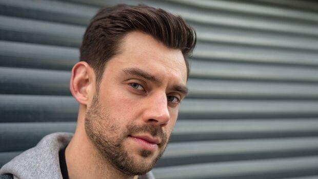Ein Seitenscheitel verdeckt dünnes Haar an den Schläfen