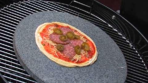 Ein echter Sizilianer grillt eine Steinofenpizza mit Salami und Pepperoni
