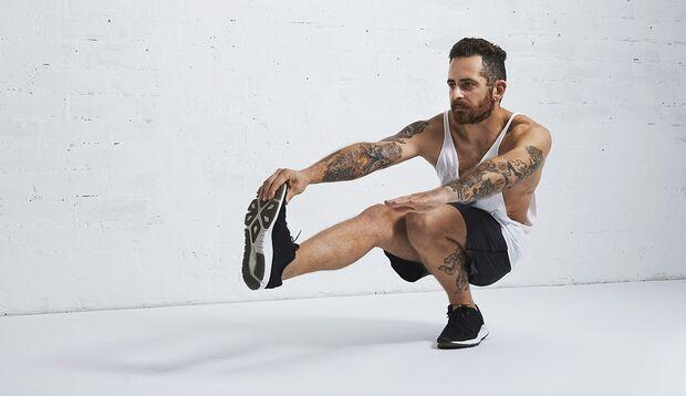 Einigen Athleten fällt der Pistol Squat leichter, wenn Sie den ausgestreckten Fuß mit der gleichseitigen Hand umfassen.
