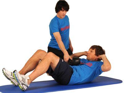 Impact-Crunches: Bei dieser Übung schlägt der Partner im höchsten Punkt mit dem Boxhandschuh auf den Bauch – das verstärkt die Endkontraktion.<br /> 15 Wiederholungen, 3 Sätze