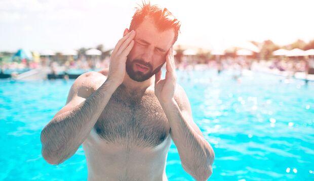 Kranker Mann im Urlaub am Pool