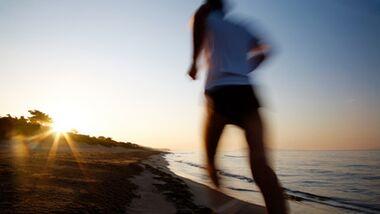 Läufer am Strand beim Sonnenuntergang