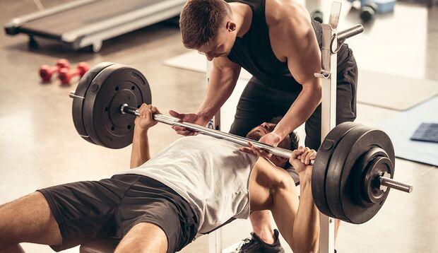 Lassen Sie sich die Hantel von einem Trainingspartner anreichen