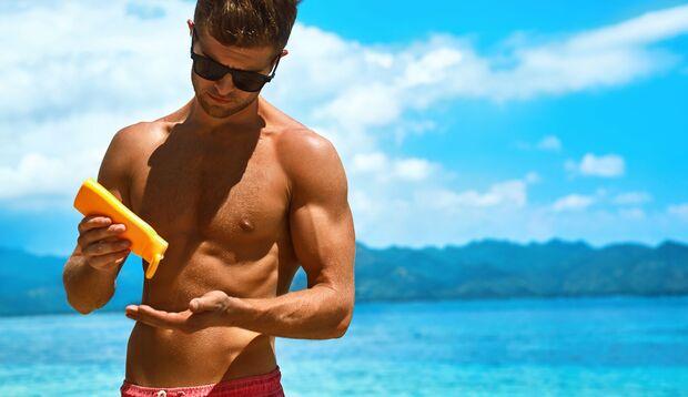 Mann cremt sich am Strand mit Sonnenschutz ein