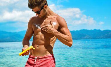 Mann cremt sich mit Sonnencreme ein