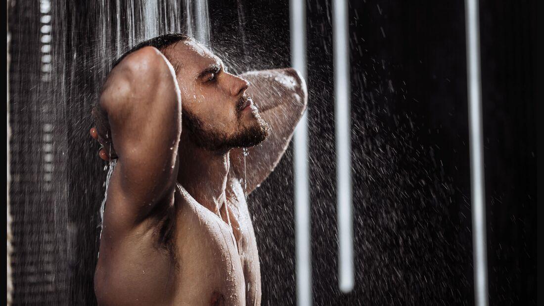 Mann duscht und genießt