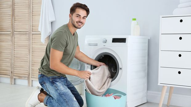 Mann füllt Waschmaschine