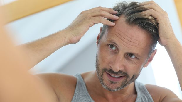 Mann schaut sich Haare an