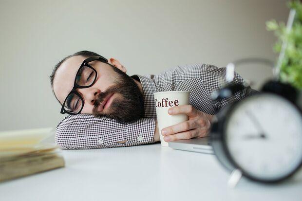 Mann schläft mit Kaffee in der Hand auf dem Tisch