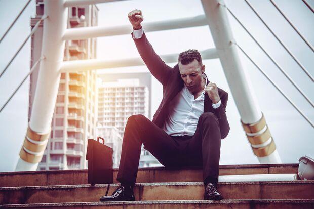 Mann sitzt auf Treppe und streckt die Faust in die Luft