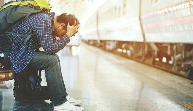 Mann sitzt krank am Bahnsteig