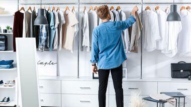 Mann sortiert Kleiderschrank
