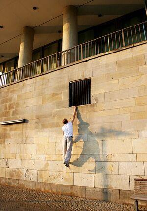 Traceur springt an einem Fenstervorsprung hoch