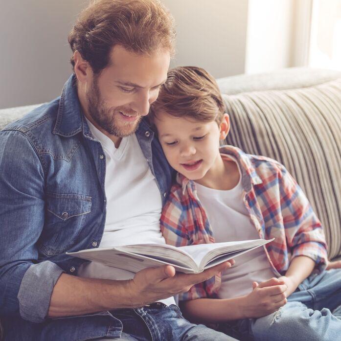 Vater hält seinen kleinen Sohn im Arm und liest ihm etwas vor. Beide schauen in ein Buch.