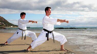Zwei Männer bei Karateübungen am Strand